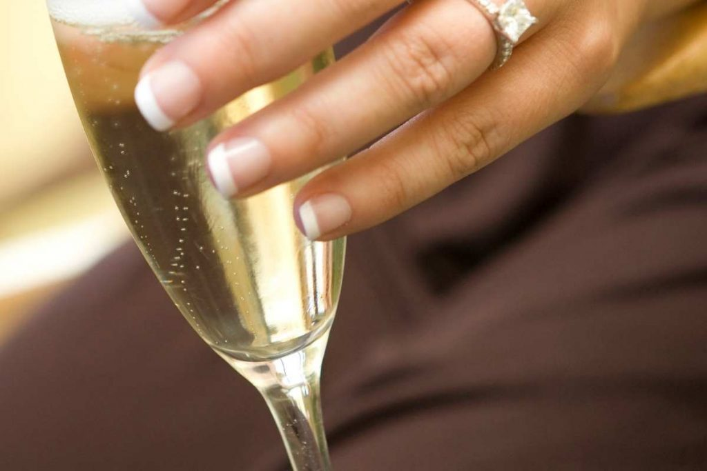 Holding a champagne glass from rim