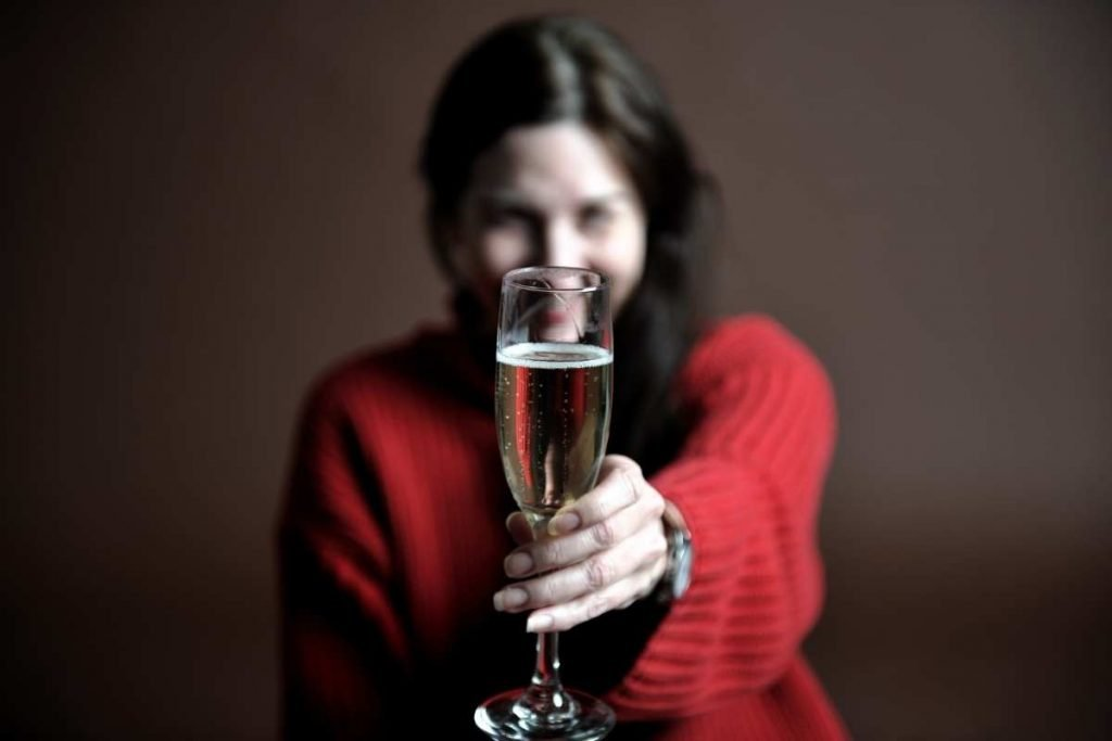 Holding a champagne glass from stem